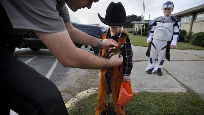 Aiken County Sheriff's Deputy Austin Lancaster pins a badge onto Matthew Murphy, 4, while his brother, Noah Murphy, 8, looks on during the Aiken County Sheriff's Department Halloween event.  This year's event will be a drive through due to the pandemic.