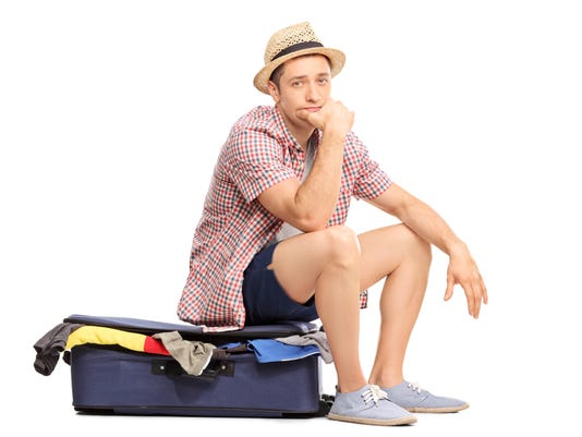 Sad male tourist sitting on bag full of clothes