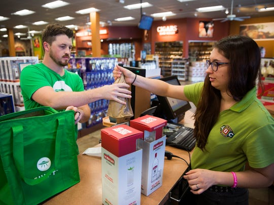 Krystyne Young hands purchased bottles of wine to Jason Nigh, a Shipt shopper, on Friday, Oct. 21, 2016, at ABC Fine Wine and Spirits in East Naples. Nigh works part-time with Shipt.