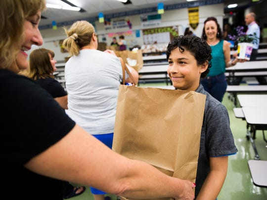 Jeison Diaz takes a bag of food during a distribution on Thursday, April 20, 2017, at East Naples Middle School in East Naples. The Collier Harvest Foundation hosts the event every third Thursday of the month. The agency distributes groceries to 50 families, coinciding with the school's Title 1 parent meetings.