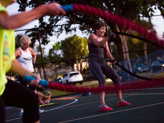 Kathy Curtis throws the ropes as a part of a rotation workout during an early morning fitness class at Fleischmann Park on Wednesday, Nov. 22, 2017. Bo Crosby has been leading outdoor fitness camps at the park for eight years.