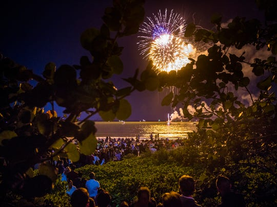 People watch the fireworks display from the boardwalk and the beach during the New Year's Eve fireworks at the Naples Pier on Sunday, Dec. 31, 2017.