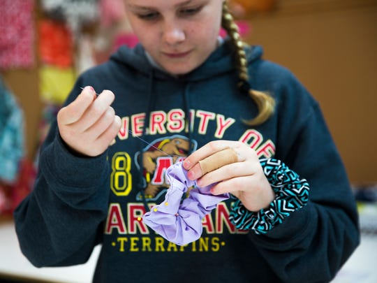 Audrey Langeloh, 12, hand stitches a scrunchy during