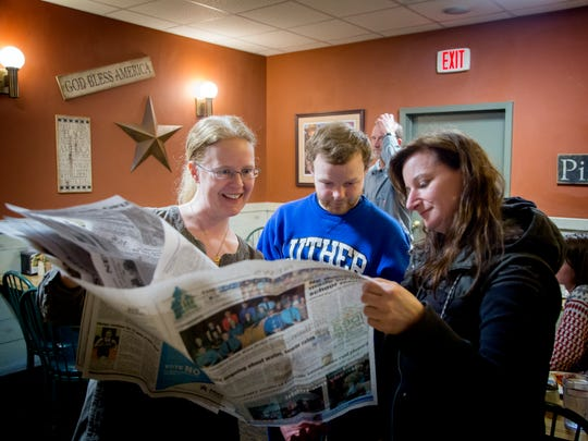 Tabita Green, Geoffrey Dyck, and Emily Neal look at newspaper add after a Decorah Power meeting at Pizza Ranch in Decorah Thursday, March 22, 2018.