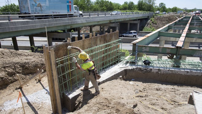 A worker put up a wall along North Keystone Avenue, where it crosses 86th Street, during road construction in Indianapolis in May 2015.