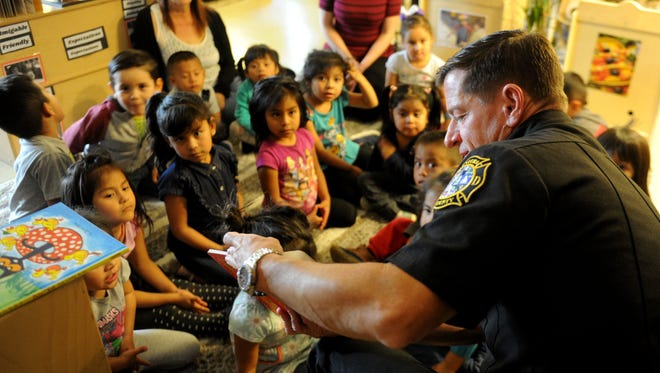 Ventura County Fire Chief Mark Lorenzen reads at La Escuelita in Oxnard as part of Take Five and Read. Celebrity readers read to young children Friday throughout Ventura County to kick off the third annual Take 5 and Read to Kids campaign.