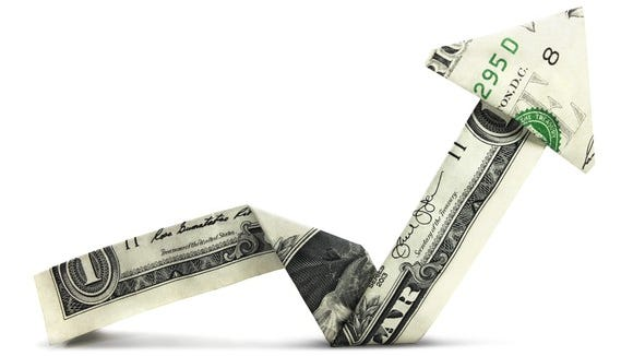A dollar bill folded as an arrow that goes down but then back up again.