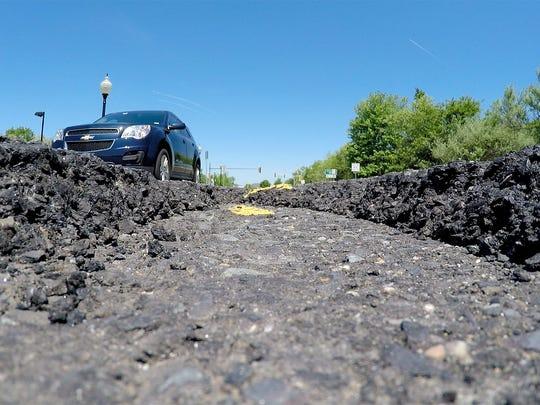 A car rolls past a a pothole outside Brick House Tavern