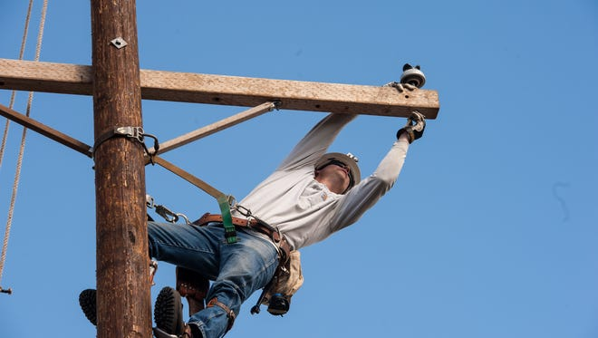 A JCP&L employee demonstrates working high up on a pole at the utility's Howell training facility.