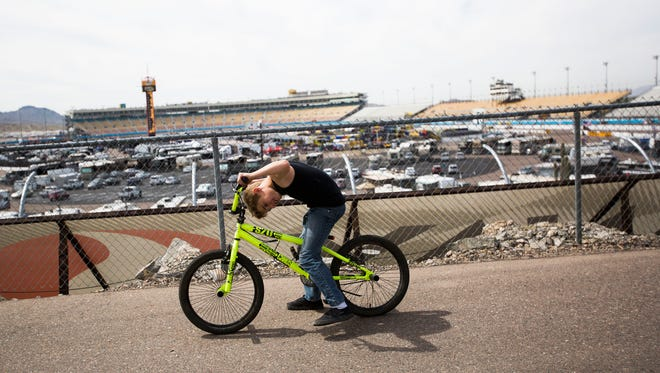 A boy pauses to check his bike overlooking the track during the first day of the NASCAR Good Sam 500 on Friday, March 11, 2016, at Phoenix International Raceway in Phoenix, Ariz.