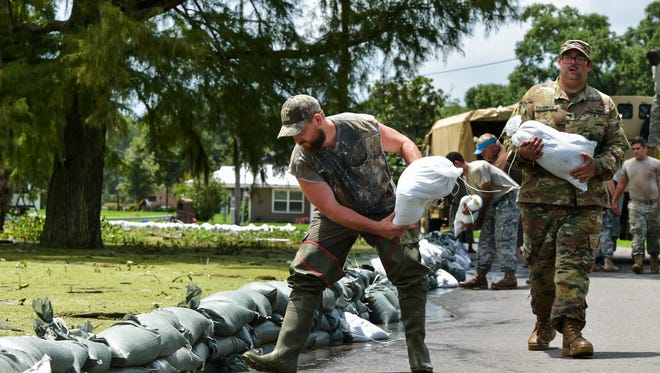 Lake Arthur, La., residents receive help from the Army National Guard to build sand bag wall to keep flood waters from the city on Wednesday, Aug. 17, 2016.