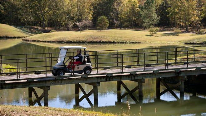November 11, 2016 - A golfer drives a cart across a bridge at Mirimichi Golf Course in Millington, Tenn.