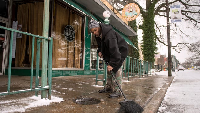 "January 6, 2017 - Keith Rawlings sweeps snow and ice off the sidewalk in front of Beauty Shop restaurant in Cooper-Young. The neighborhood tentatively won ""historic overlay district"" status Tuesday. (Brandon Dill/Special to The Commercial Appeal)"