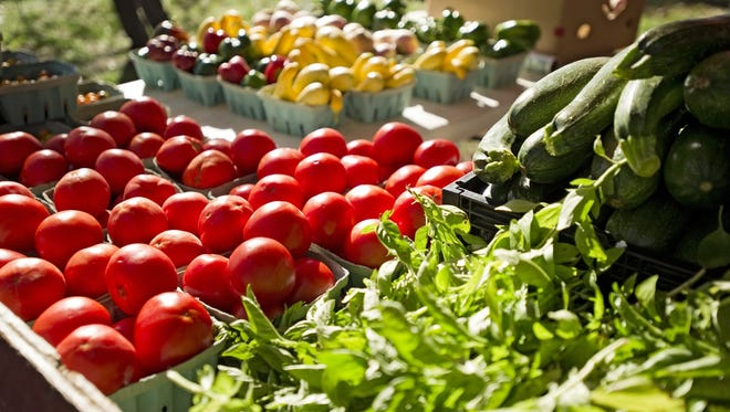 Fresh basil, cucumbers, peppers and a variety of tomatoes are among the offerings at the Whitton Farms stand in the Farmers Market at the Memphis Botanic Garden.
