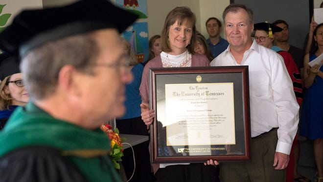 May 26, 2016 - Katrina Stevens, center, and her husband Randy Stevens, right, look on as their daughter Rachel Kay Stevens is awarded a posthumous Masters of Occupational Therapy diploma by UTHSC Chancellor Dr. Steve J. Schwab (left) at a ceremony in the Rachel Kay Stevens Therapy Center, named after their late daughter. (Brandon Dill/Special to The Commercial Appeal)
