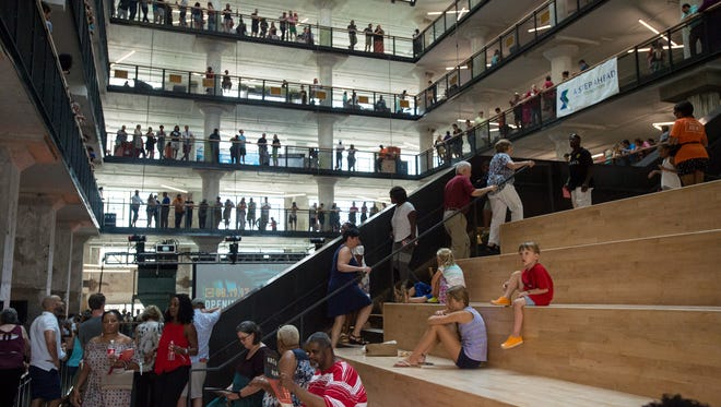 "Visitors crowd the central atrium during the grand opening celebration of the Crosstown Concourse building in Memphis. Built by Sears in the late 1920's, the building employed thousands of workers until it was shuttered in the mid 1990's. In 2010 work began to transform the building into a ""vertical urban village"" which which is now home to dozens of tenants including art galleries, restaurants, fitness centers, education organizations, health care facilities, places of worship, banks as well as residential living spaces."