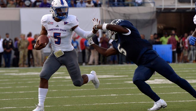 Tennessee State University quarterback Treon Harris, left, runs past Jackson State University defensive back Dario Robinson in the first half of the Southern Heritage Classic football game between TSU and JSU at Liberty Bowl Memorial Stadium in Memphis, Tenn. (Brandon Dill/Special to The Commercial Appeal)