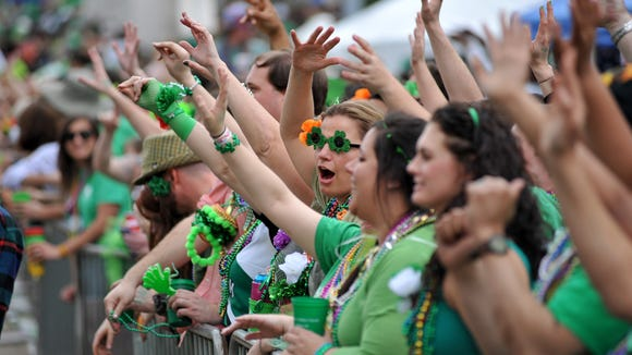 People yell for throws from passing floats on Pearl Street during the Mal's St. Paddy's Parade in downtown Jackson Saturday.