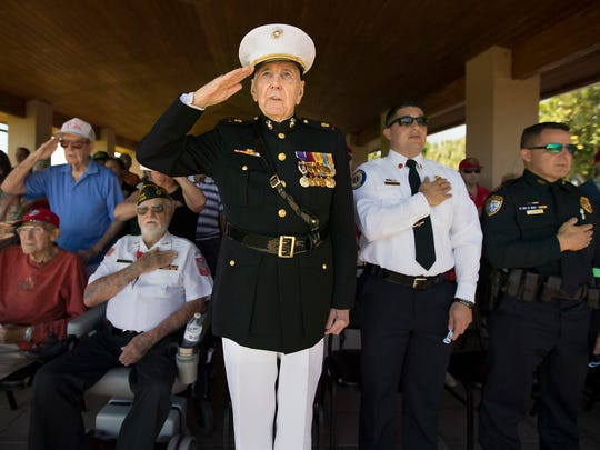 Retired U.S. Marine Lieutenant Walter L. Dugan honors the pledge of allegiance Sunday during an Iwo Jima remembrance ceremony at the Veterans Memorial at Four Mile Cove Ecological Preserve in Cape Coral. More than 100 people attended the annual event. U.S. Marines captured the island of Iwo Jima from the Japanese Imperial Army in a battle that raged from Feb. 19 to March 26, 1945.