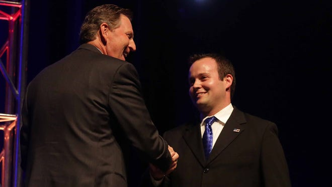 Bob Vander Plaats, left, greets Josh Duggar, executive director of the Family Research Council Action, following Duggar's speech during the Family Leader Summit in Ames on Saturday, Aug. 9, 2014.