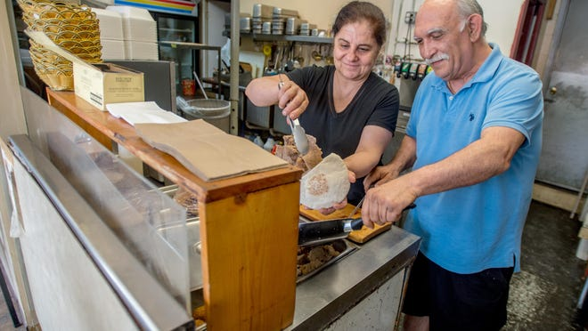 Gabe Haddad, right, and his wife, Nidal, construct a gyro at their Mediterranean restaurant, Haddad's, at 1010 W. Main St., Peoria. Haddad's is well known for its lunchtime pushcart service in Downtown Peoria, a service that has been suspended due to the coronavirus shutdown.