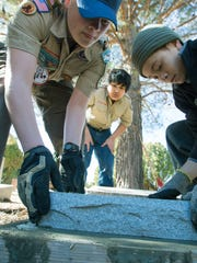 Gunnar Smith, 15, left, works with his friends Lazaro Quezada, 11, center, and Jaylen Purvis, 13, who are both Boy Scouts, at Masonic Cemetery on Saturday, January 27, 2018.