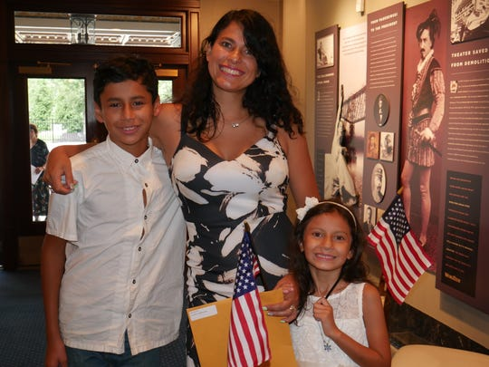 Carmen La Serna stands with two of her children, Danny and Isabella, after a naturalization ceremony Friday at the Bardavon 1869 Opera House in Poughkeepsie.