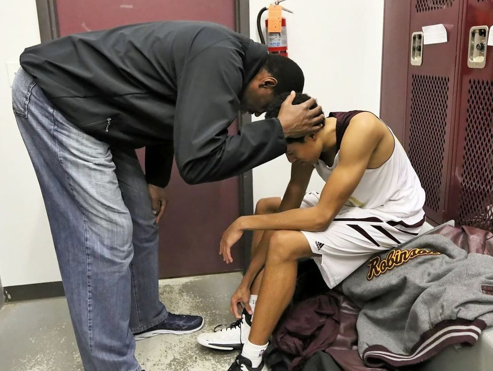 Spurs great David Robinson shares a quiet moment with his youngest son, Justin, in the San Antonio Christian locker room after the Lions' 51-45 win over TMI on Tuesday night.
