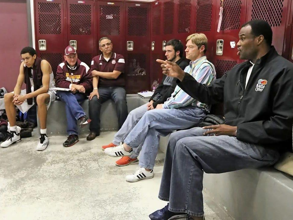 San Antonio Christian senior forward Justin Robinson, far left, listens as his father, David Robinson, talks to the team Tuesday night.