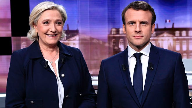 The two French presidential candidates, National Front party's Marine Le Pen, left, and Emmanuel Macron, pose before the start of their televised debate on May 3, 2017, ahead of Sunday's runoff vote.