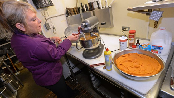 Tina Palmisano adds milk to the masa mixture. A bowl of sweet potato (right) will be added to make a dessert tamale with a pecan glaze topping.