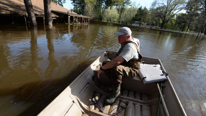Tom Foster takes a boat along flooded portion of Caddo Lake between Ferry Lake Road and  Ferry Lake School Road. Many of the homes in that area of Caddo Lake have been flooded out.