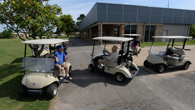 A group of galfers chat by the newly refurbished club house at Shreveport's Huntington Golf Course. The city ownerd facility has recently undergone renovations with the hopes of increasing membership and drawing more recereational golfers ot the area.