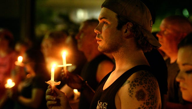 A supporter stands with a candle as he and several hundred gathered at the Caddo Parish Courthouse for a candlelight vigil for the victims of the Orlando night club shooting.