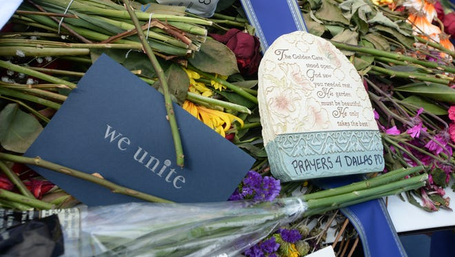 """Flowers and """"We Unite"""" cards are just some of the items left behind at a memorial for the five fallen officers at Police head quarters in Dallas Texas."""