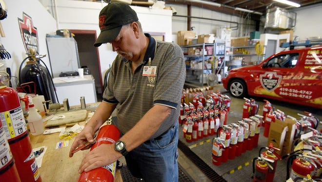 Dan Feldman checks fire extinguishers at Schmidt Security Pro.