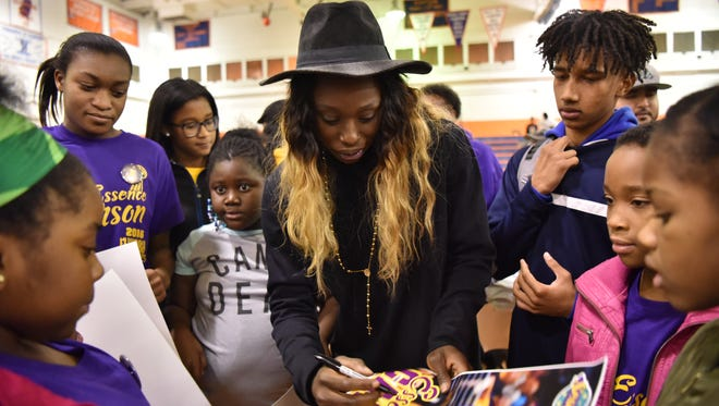 Paterson native Essence Carson, who was a star player for Rutgers and the WNBA's NY Liberty and now with the Los Angeles Sparks, signs posters for fans at Eastside High School in Paterson where her career started.