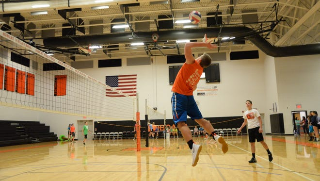 A Northeastern student skies to return a volley during the Silence Ends Here Volleyball Tournament at Northeastern High School on Sunday, Dec. 4, 2016.