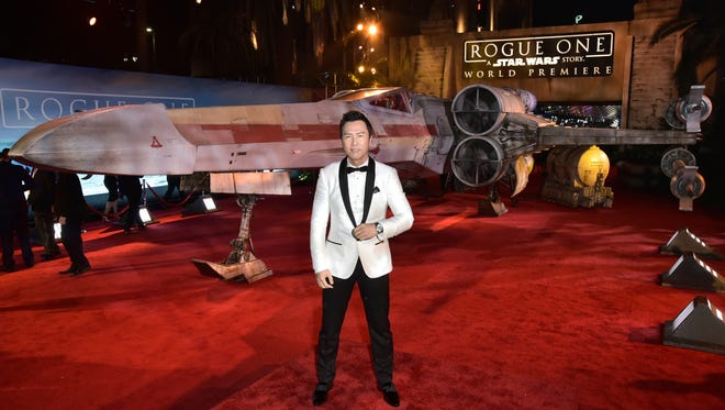 'Rogue One' star Donnie Yen poses in front of the X-wing in front of his movie's premiere.
