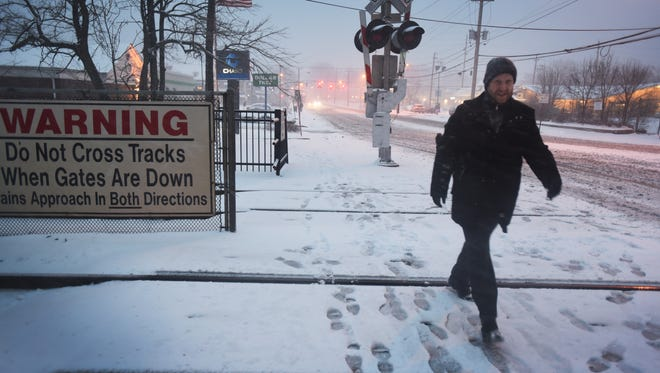 A commuter walks across the tracks at Fair Lawn station while its snowing in Fair Lawn on Feb. 9th, 2017.