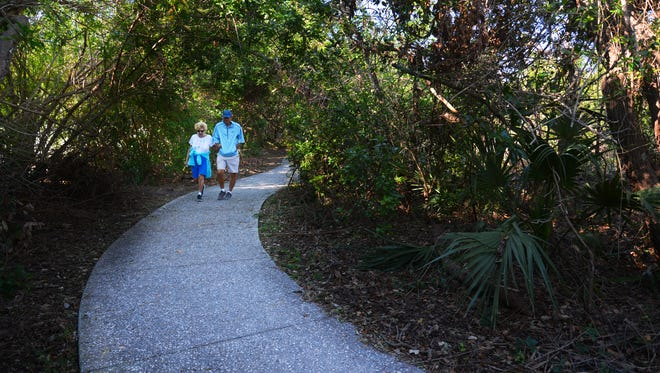 Beverly and Trent Magner of Indiana walk down the wooded path that winds its way through the 9.6 acres in Jetty Park that the county owns and leases to Port Canaveral for $1 a year.