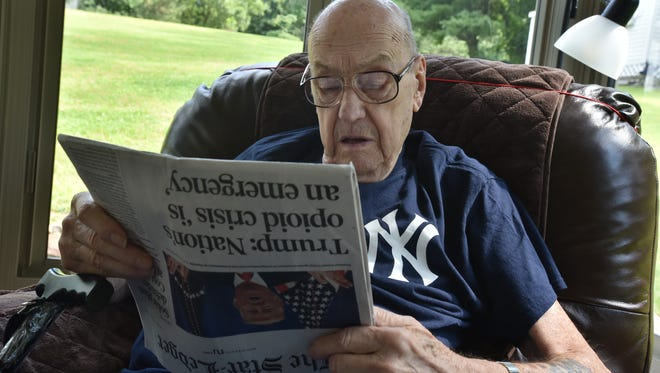 Joseph Hahn, who served in the Korean War and lost his toes and fingers there due to frostbite while on a reconnaissance mission, reads his paper in his home in Lincoln Park. Photo: Marko Georgiev/NorthJersey.com