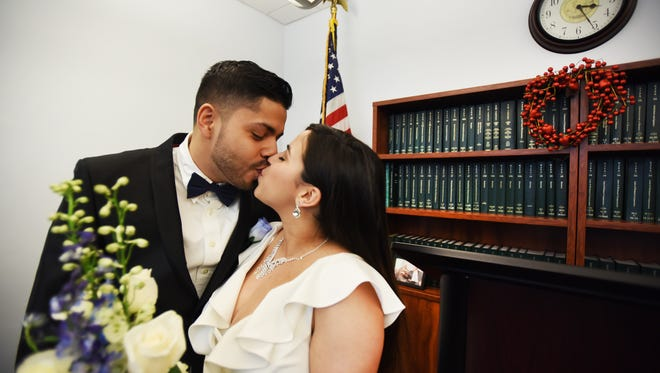 Amyah Gaither (age 23) of Ridgefield Park and her husband Isiah Silva (age 25) of Ridgefield Park, kiss each other following their marriage ceremony performed by Bergen County Clerk John Hogan at the Bergen County Administrative Buildings in Hackensack on 02/14/18.