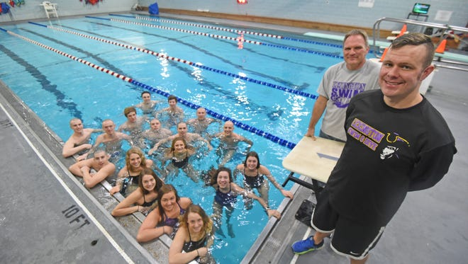 Lexington head coach Brock Spurling and diving coach Rob Roth with the 14 swimmers and three divers who have qualified for this week's state meet in Canton.