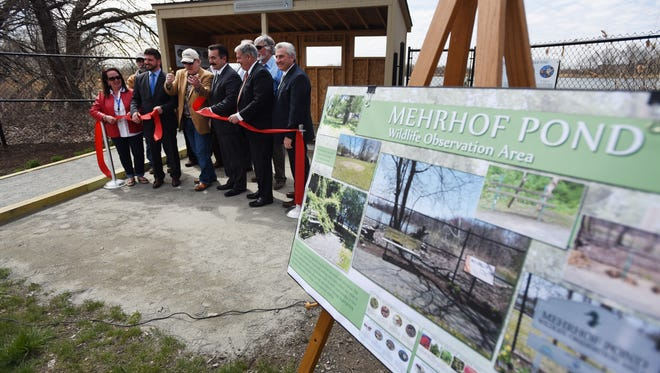 Officials including, Captain Bill Sheehan (center), Chairman of Meadowlands Conservation Trust perform the ribbon cutting during the the Mehrhof Pond Wildlife Observation Area Ribbon Cutting Ceremony in Little Ferry on 04/24/18.