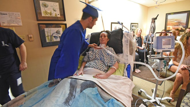 Ontario graduate Dom Castelvetere hugs and kisses his mother Beth Popa Castelvetere after being awarded his high school diploma early in the chapel at OhioHealth  Thursday evening to allow his mother to be there.