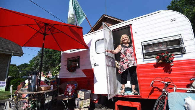 "Beth Nunn, owner of A Heritage House at 1170 Lexington Avenue, enjoys the ""Glamper"" she has on display to help celebrate 35 years of business."
