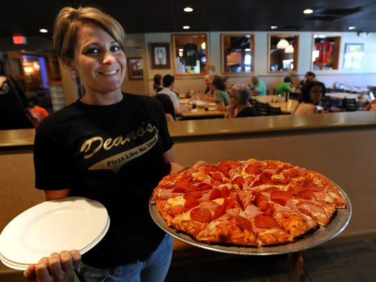 Dine for the Diner, a day in which many local restaurants — including Dean-O's Pizza — will donate 10 percent of their sales to St. Joseph Diner. Friday, April 6, 2012. Manager Jill Comb brings out one of their specials.