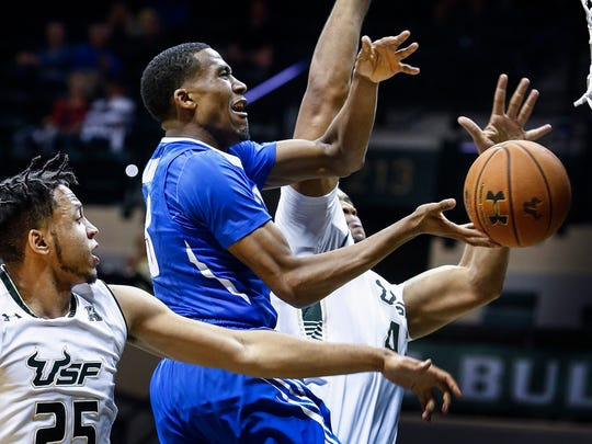 University of Memphis guard Jeremiah Martin (middle) is fouled while driving to the basket against University of South Florida defenders Troy Holston (left) and Luis Santos (right) during the second half  of an 85-75 victory at the Sun Dome in Tampa, Florida, Thursday.