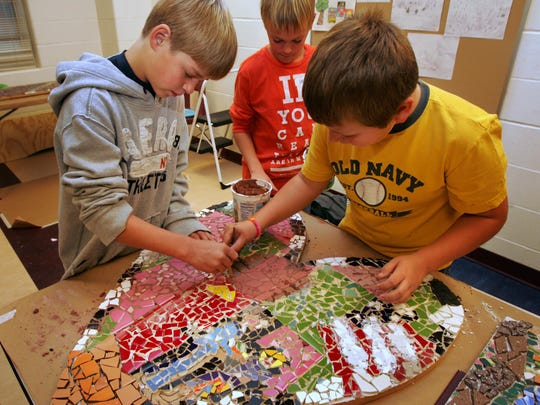 Fifth-graders Josh Johnson, Jack Lillig and Ethan Gray added grout to a mosaic at a Metro Arts Alliance workshop in 2011 at Ashland Ridge Elementary School. They and their classmates helped the artist Concetta Morales make a series of mosaics for the school.